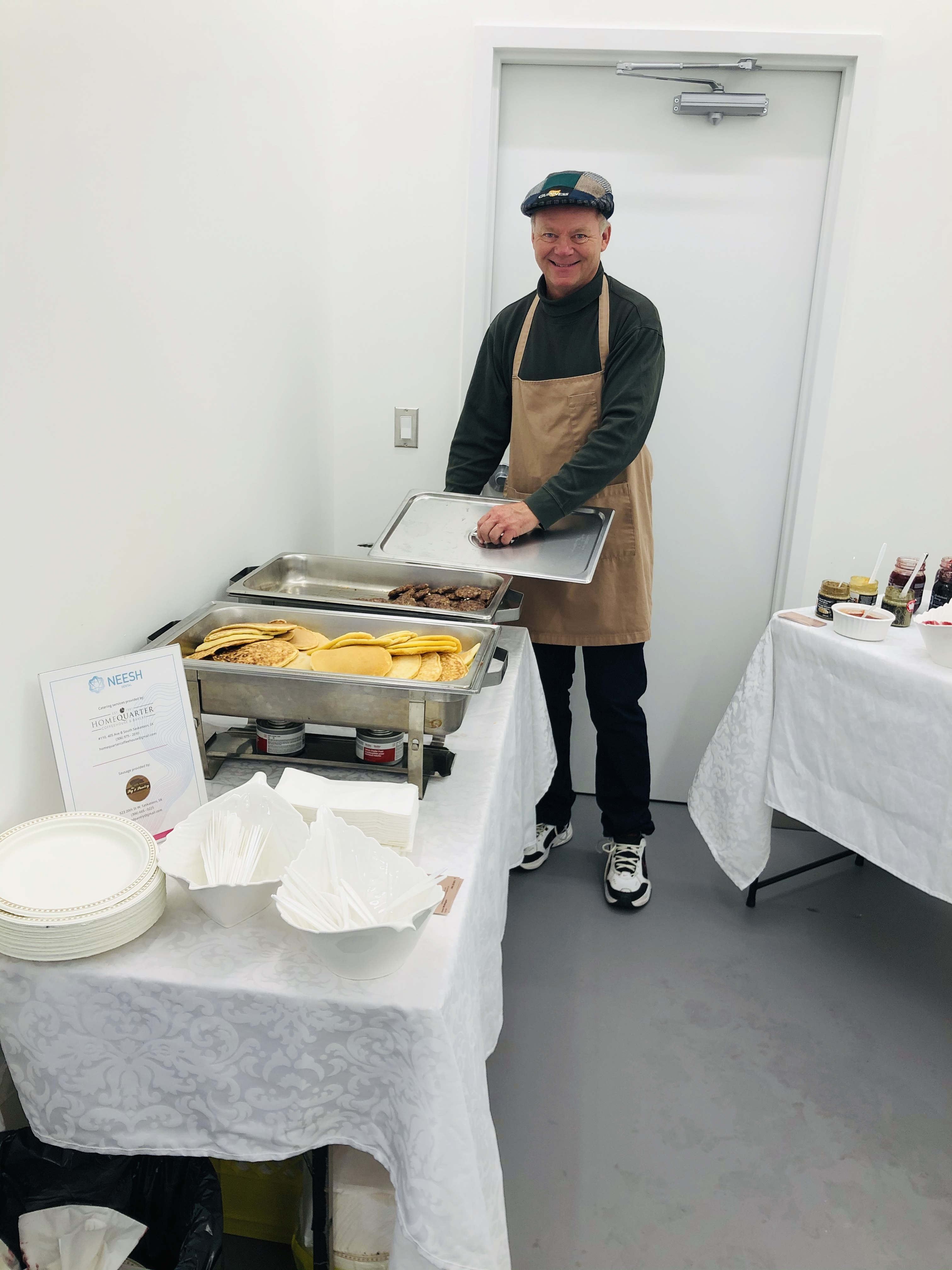 A man smiles at a serving area for a pancake breakfast, hosted for the grand opening of Neesh Dental in Saskatoon Saskatchewan.
